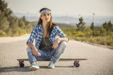 Woman sitting over a skateboard