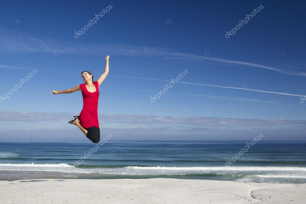 Beautiful woman in red jumping