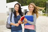 dospívající studenty drží poznámkové bloky a s úsměvem