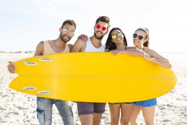 friends together holding a surfboard