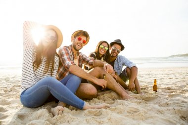Friends drinking a cold beer at the beach