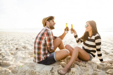 Young couple at the beach drinking beer