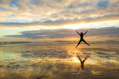 Woman jumping  at the sunset