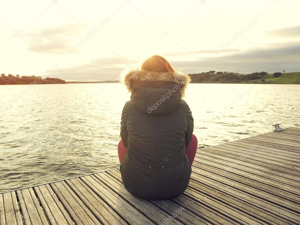 Woman sitting close to a lake