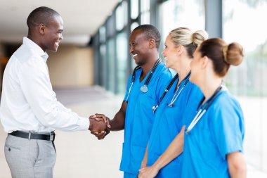 medical representative handshaking with doctors in hospital