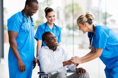 doctors greeting disabled patient