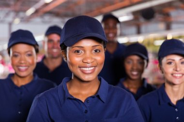 Young african factory worker with colleagues
