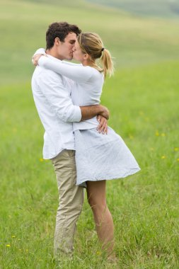 young couple kissing on green field