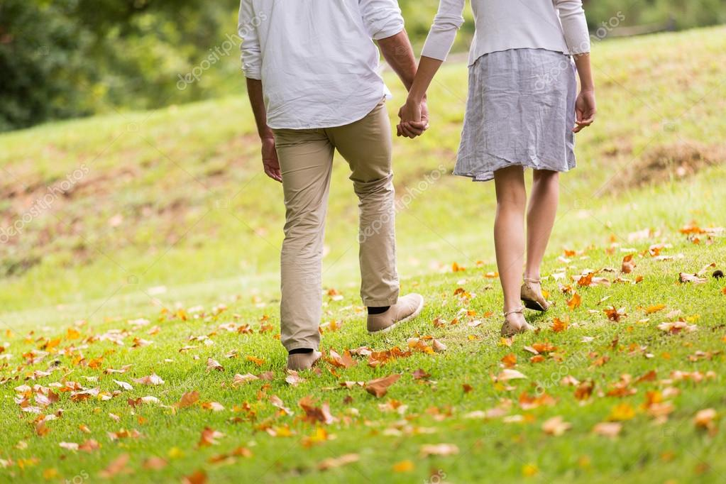 Couple holding hands walking in park