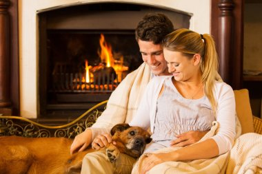 Couple sitting by fireplace with their pet dog