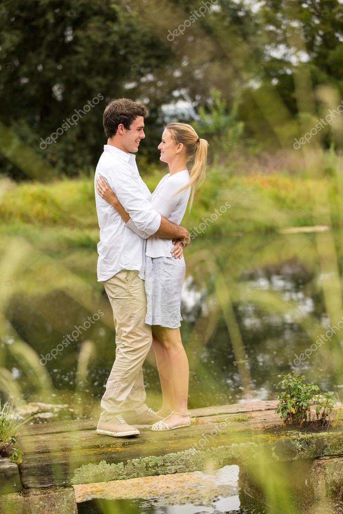 couple hugging on lake pier