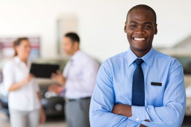 african car salesman looking at the camera