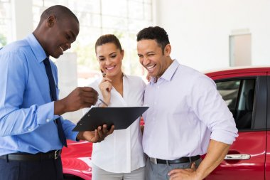 Car dealer explaining sales contract to couple