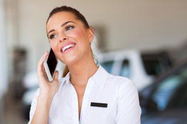 car saleswoman talking on cell phone