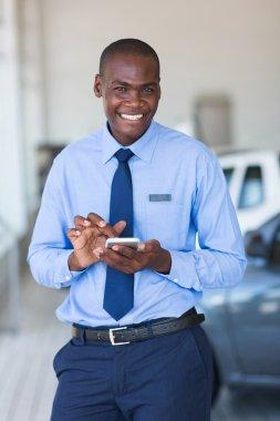 Car salesman using smart phone