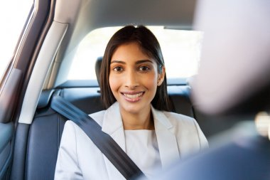 businesswoman sitting in car backseat