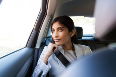 young indian businesswoman sitting in car