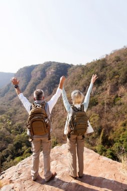 hikers with arms open on mountain cliff