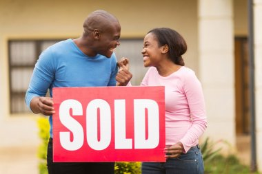 couple holding sold sign