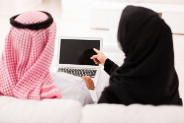 muslim couple using laptop computer