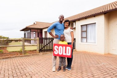 family near home with sold sign