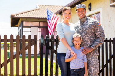 Cheerful young military family standing together near house stock vector
