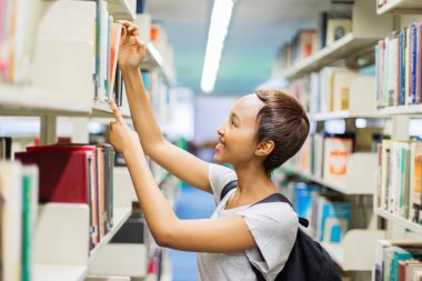 student searching for book in library