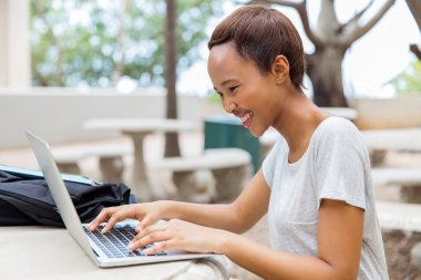 female african student working on laptop