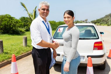 driving instructor and learner driver handshaking