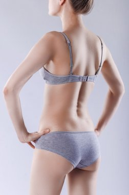 Slim woman in gray underwear