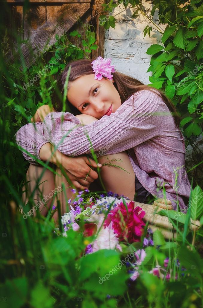 Tender woman resting in grassy thickets with a beautiful bouquet