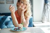 Glückliche niedliche junge Frau, die süßes, leckeres Dessert in einem Café im Freien isst. Leckeres Essen, okay Lebenskonzept.