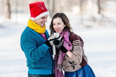 Happy couple having fun and drinking hot tea on rink outdoors.