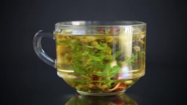 horký bylinný čaj z různých bylin ve skleněném poháru na černém pozadí