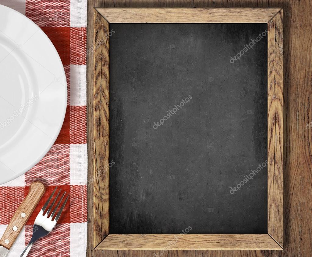 Vista superior de la pizarra de men en mesa con plato for Tenedor y cuchillo en la mesa
