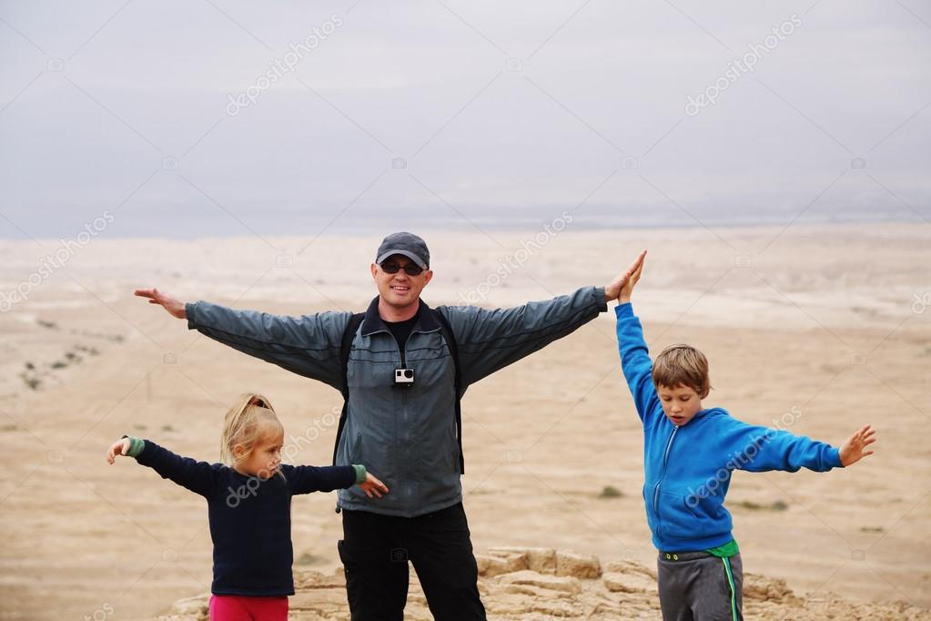 father hiking with  kids in the desert