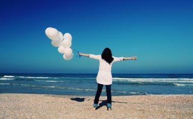 Woman holding white balloons