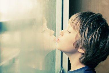 Boy looking through window