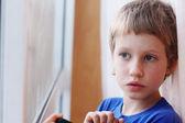 Fotografie Boy looking through the window