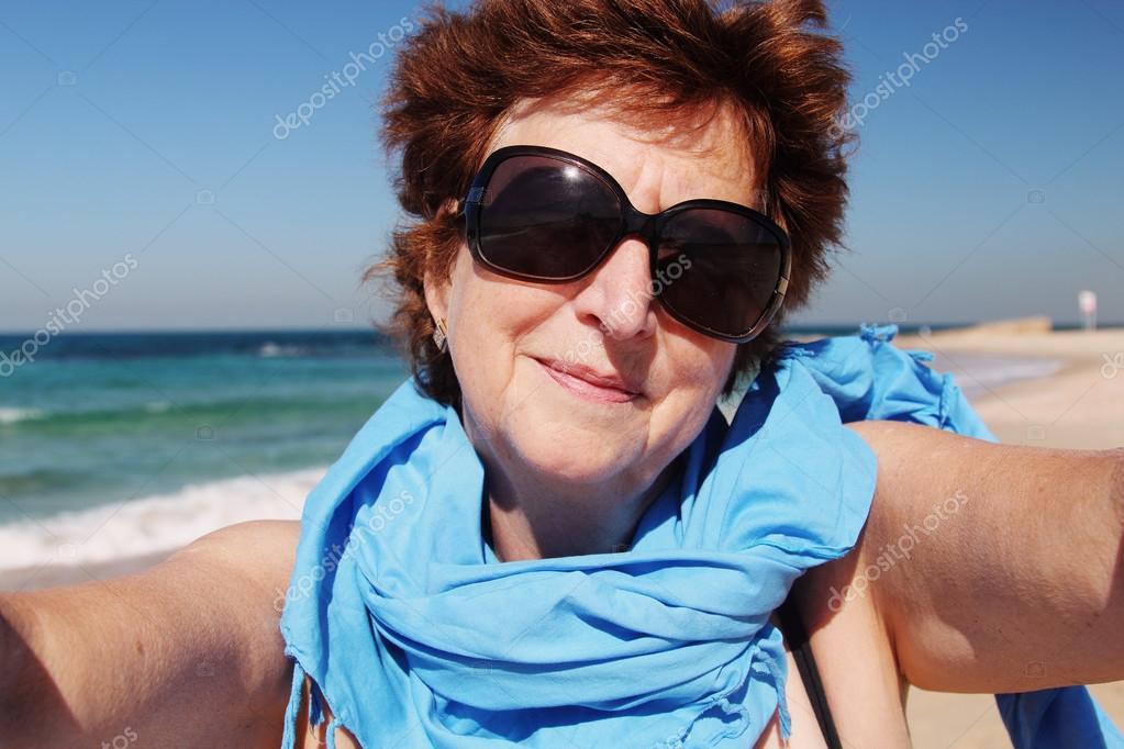 Happy senior woman on beach