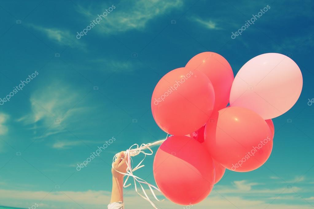 Hand holding red balloons