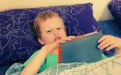 Fotografie Boy lies in bed and plays