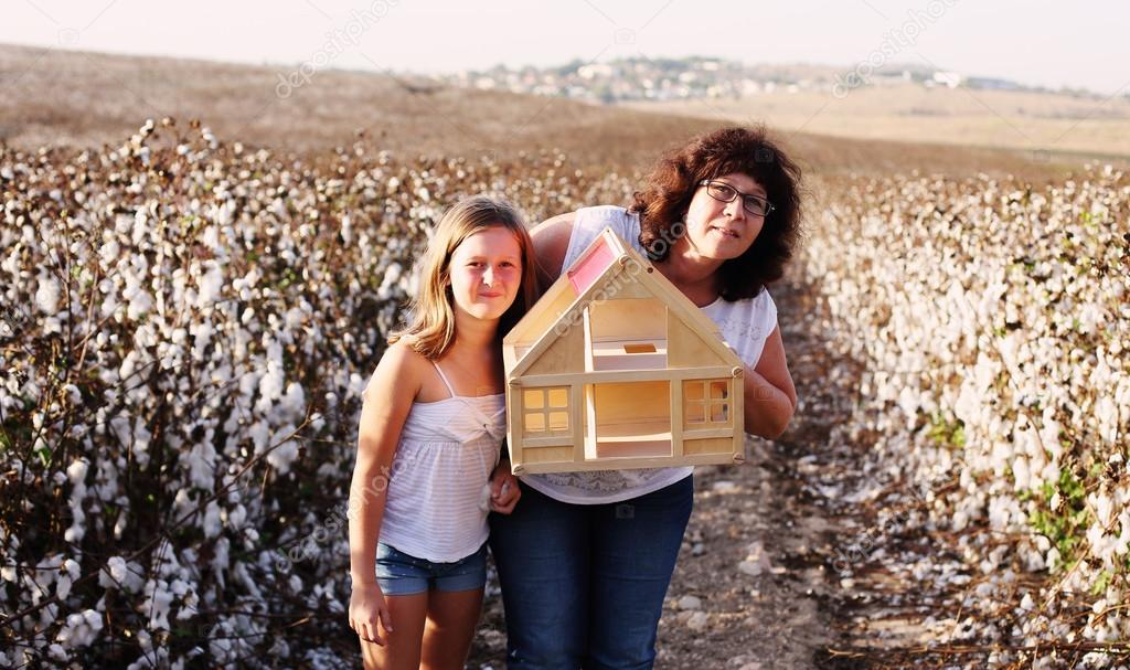 Mother and her daughter with wooden house