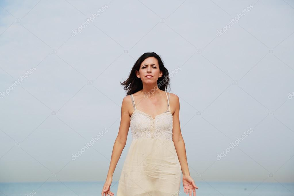woman standing on the shore of the beach