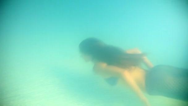 Krásná žena v růžové bikiny, potápění a plavání pod vodou