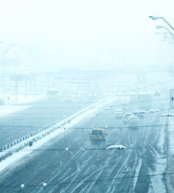 Snowy winter road with cars driving on roadway in snow storm