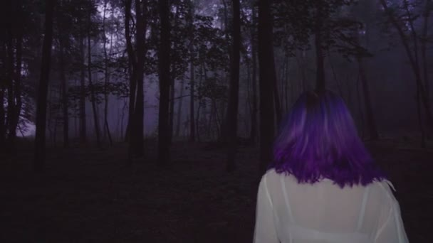 Back view of beautiful woman in white shirt and purple hair walking in dark forest - thriller scene.
