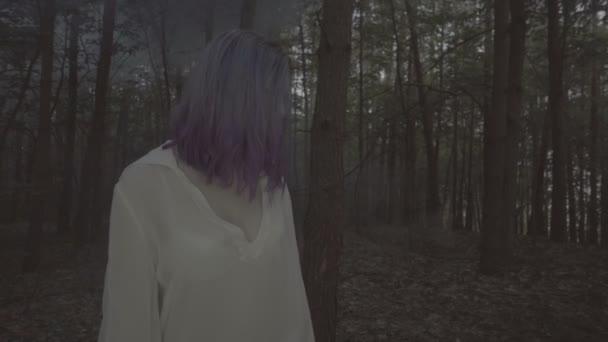 Krásná žena v bílé košili a fialových vlasech pózovných v tmavém lese. 4k video o smyslové kráse s modrým kouřem a blikajícím světlem v pomalém pohybu.