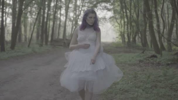Krásná žena v bílých šatech a fialových vlasech, jak kráčí po pohádkové scéně. Video o smyslné kráse mezi stromy v pomalém pohybu.