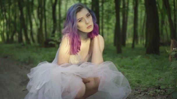 Krásná žena v bílých šatech a fialově modrých vlasech se chouří na zemi v lese a dívá se do kamery. Video o smyslové kráse v pomalém pohybu-pohádkové scéně.